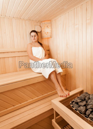 brunette woman at sauna sitting with