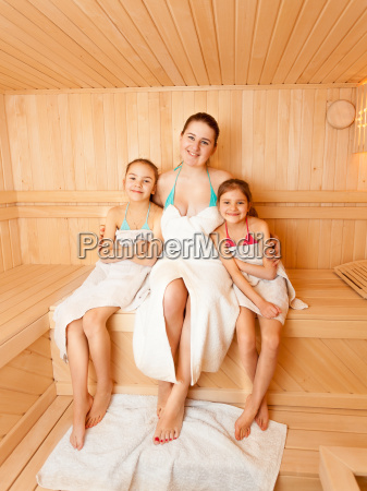 daughters with mother sitting on bench