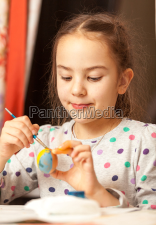 girl painting traditional easter eggs at