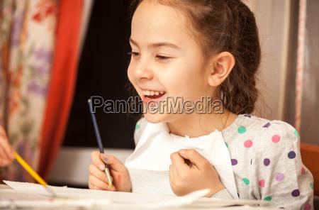 cute smiling girl holding painting brush
