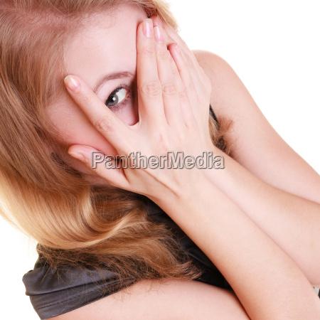 shy afraid woman peeking through fingers