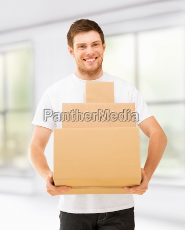 smiling man carrying carton boxes at
