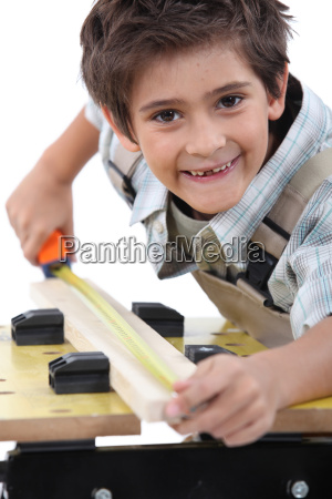 young boy measuring a piece of