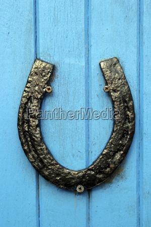 black horseshoe nailed to blue door