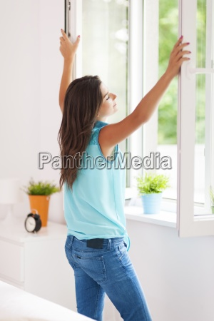 young woman opening window in living