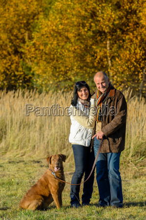 couple with dog in park autumn