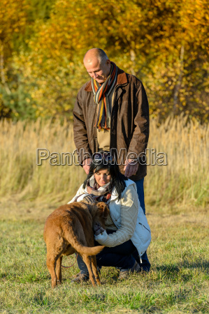 couple playing with dog sunny autumn