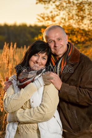 romantic couple embracing in autumn sunset