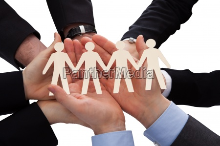 businesspeople holding human figure cutout