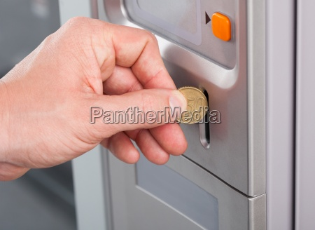 human hand inserting coin in vending