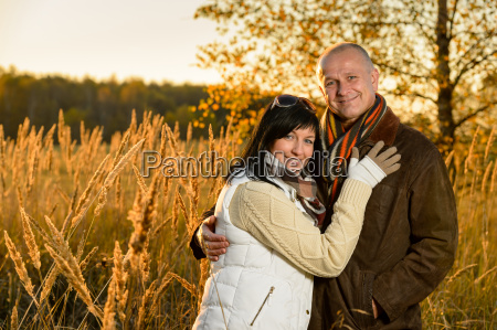 couple, embracing, in, autumn, countryside, sunset - 12388398
