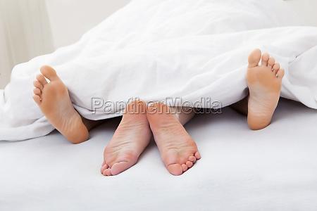 close up of couples feet sleeping