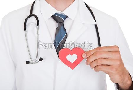 doctor holding heart shape symbol