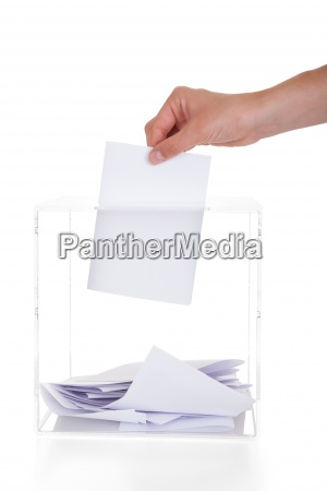 closeup of hand inserting ballot in