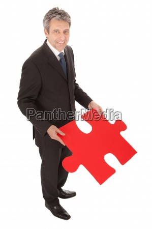 senior businessman holding a jigsaw puzzle