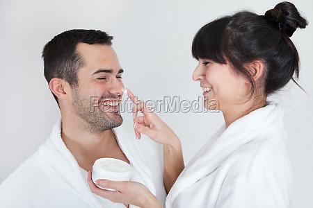 playful young couple applying cream