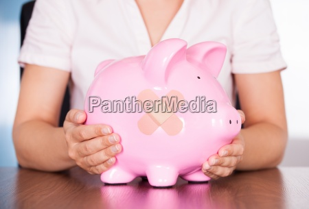 young businesswoman holding piggybank with band
