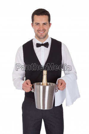 cheerful butler holding bottle of champagne