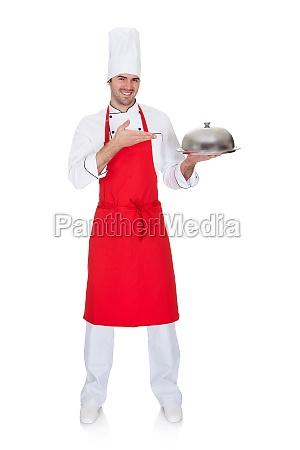portrait of cheerful chef presenting silver