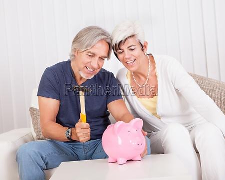 senior couple raiding a piggybank