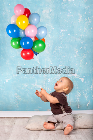 little boy playing with balloons