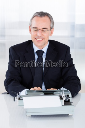mature businessman typing on typewriter