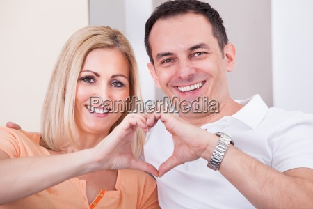 happy mid adult couple forming heart