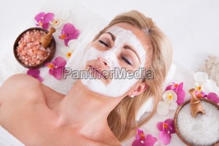 cosmetician applying facial mask on face