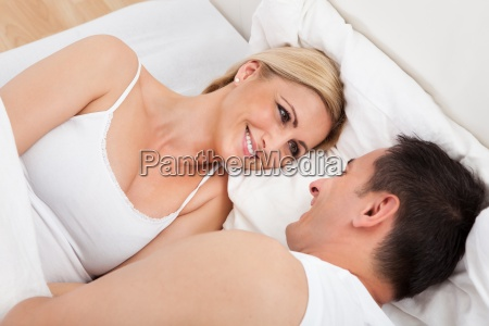 couple on bed looking at each