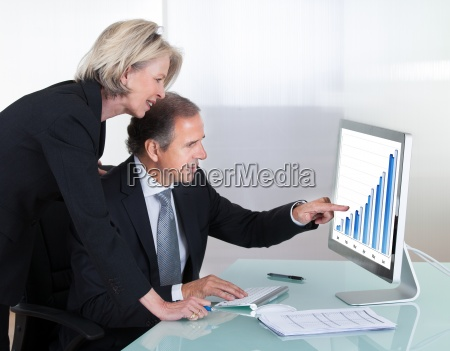 mature businessman and businesswoman looking at
