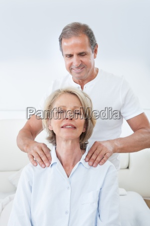 man massaging womans shoulder