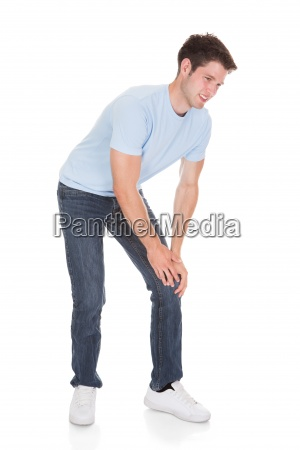 young man suffering from knee pain