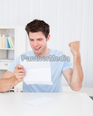 happy man looking at paper