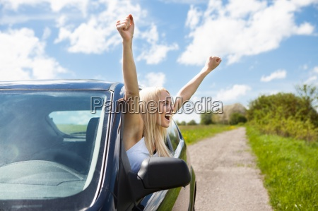 woman raising hand out of car