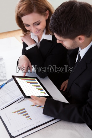 two business colleagues discussing graph