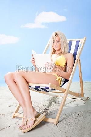 beautiful young woman in bikini reading