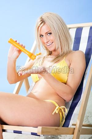 beautiful young woman in bikini applying