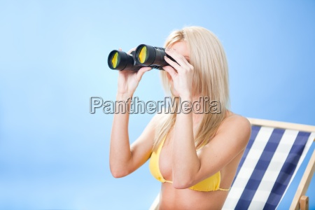 young woman in bikini looking through
