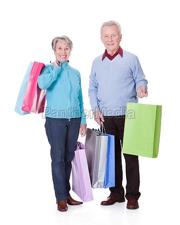 senior couple holding shopping bags