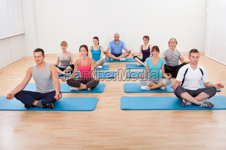 group of people practicing yoga meditating