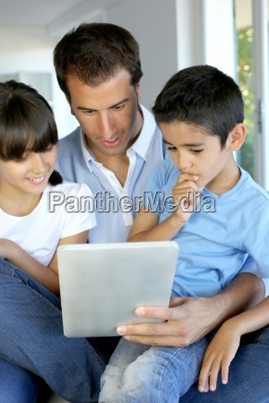 father and kids websurfing on digital