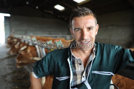 portrait of smiling breeder in barn