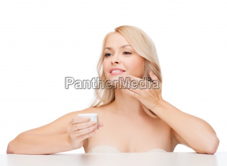 beautiful woman applying cream on her
