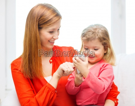 happy mother and daughter with smartphone