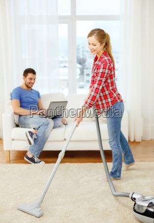 smiling woman with hoover and man