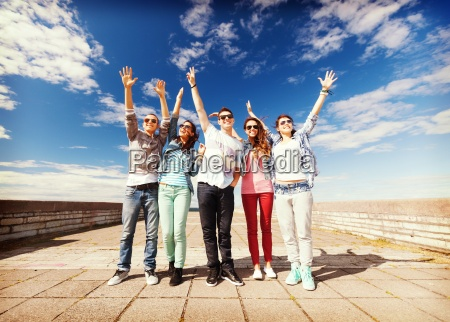 group of teenagers holding hands up