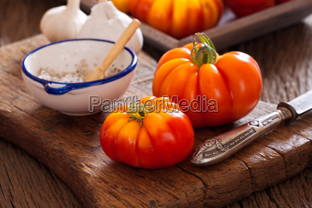 beefsteak tomatoes with knife and salt