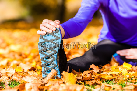 athlete while stretching in autumn foliage
