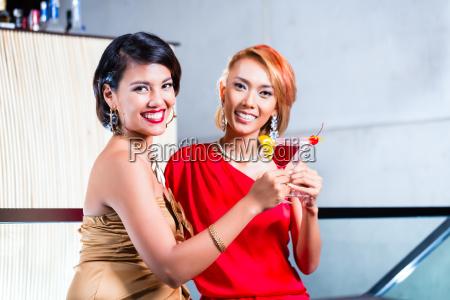 asian women drinking cocktails in fancy