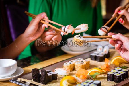 los jovenes comen sushi en asia